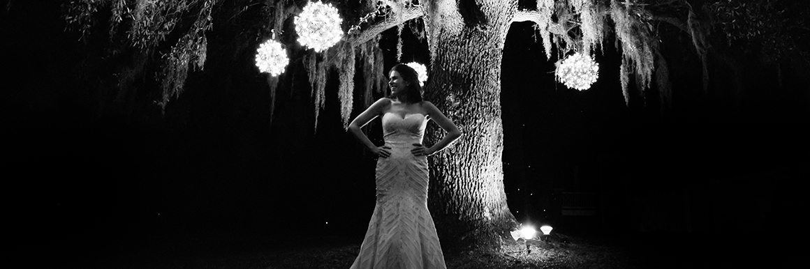 bride in wedding gown standing in front of beautiful oak tree