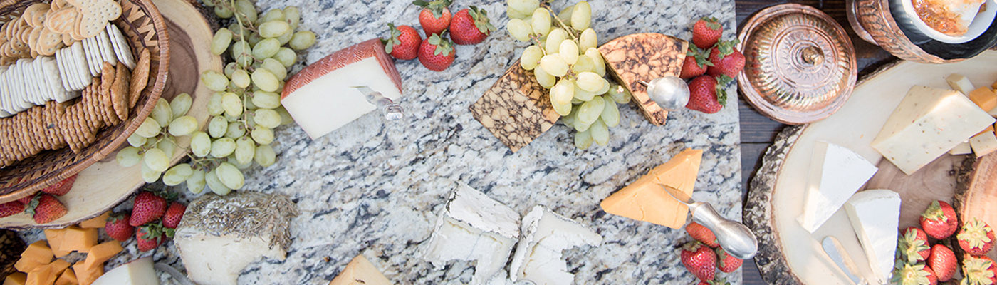 stone slab with a variety of cheeses and fruits